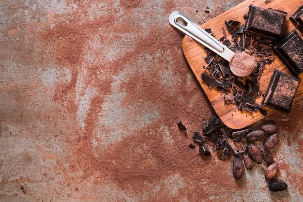 Vista elevata di pezzi di cioccolato incrinato con fave di cacao crude su fondo rustico