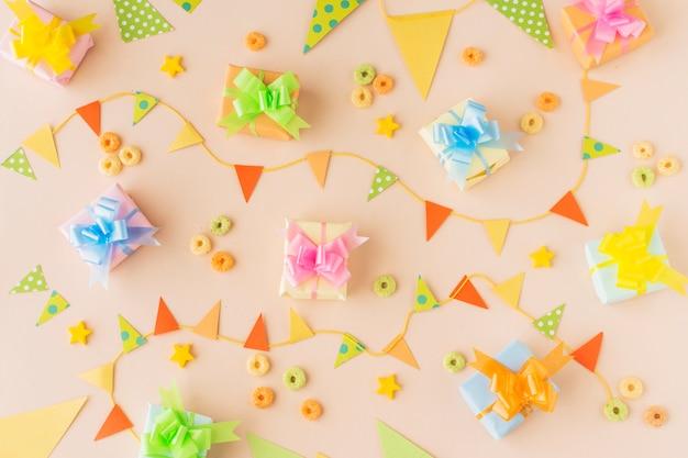 Vista elevata di regali di compleanno; bunting e froot loops caramelle su sfondo colorato