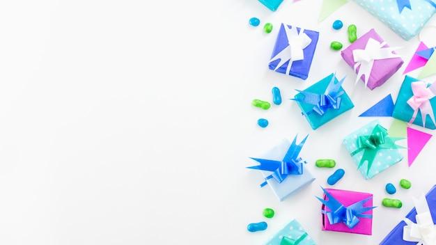 Vista elevata di regali di compleanno e caramelle su superficie bianca