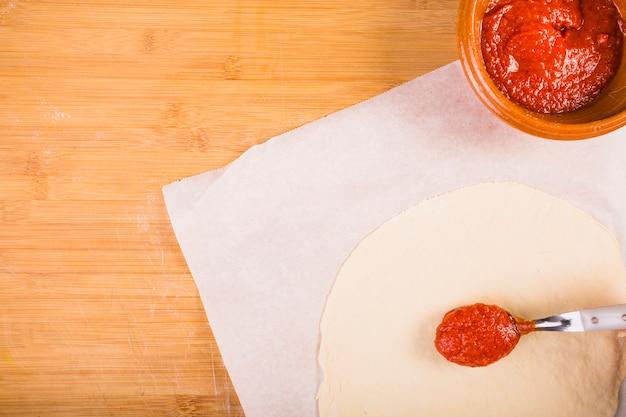 Vista elevata di salsa e pasta sul tavolo di legno