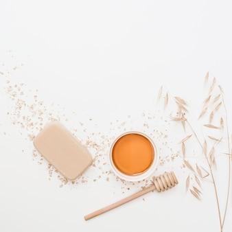 Vista elevata di sapone; miele; merlo acquaiolo del miele e silenzio sulla superficie bianca