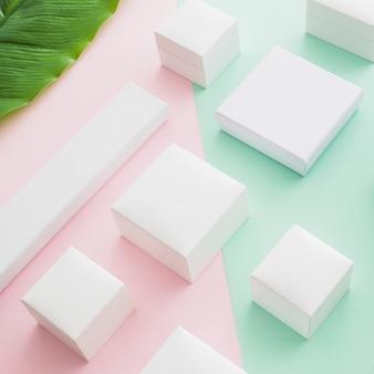 Vista elevata di scatole bianche su sfondo di carta colorata