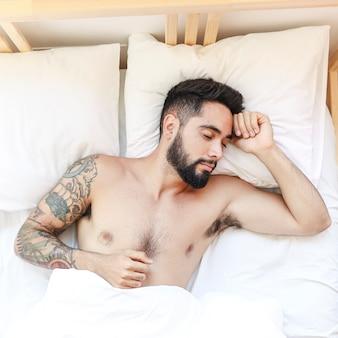 Vista elevata di un uomo senza camicia che dorme sul letto