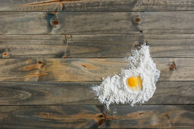 Vista elevata di uovo e farina sulla superficie in legno