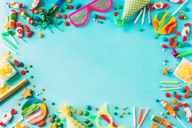 Vista elevata di vari accessori per feste di compleanno su sfondo blu