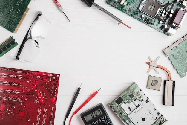 Vista elevata di varie parti del computer con strumenti e occhiali di sicurezza sulla scrivania in legno