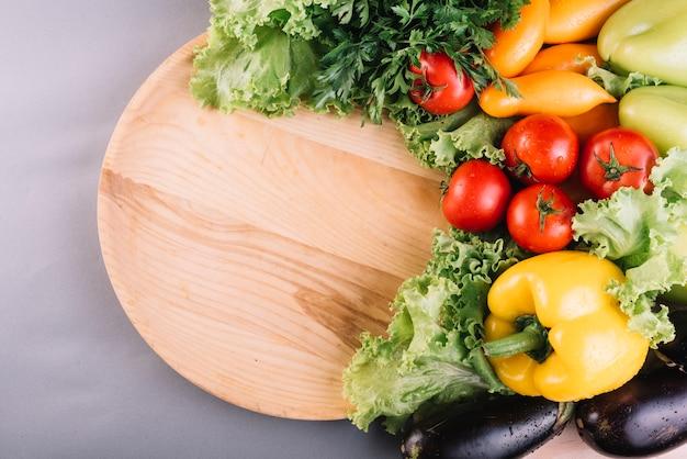 Vista elevata di verdure fresche e piatto in legno