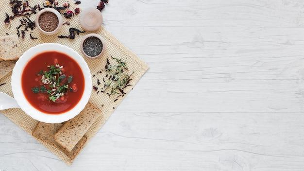 Vista elevata di zuppa e ingredienti sulla tovaglia contro tavolo in legno