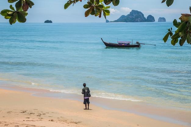 Vista esotica della spiaggia in krabi tailandia un uomo esamina la barca longtaile dalla sabbia