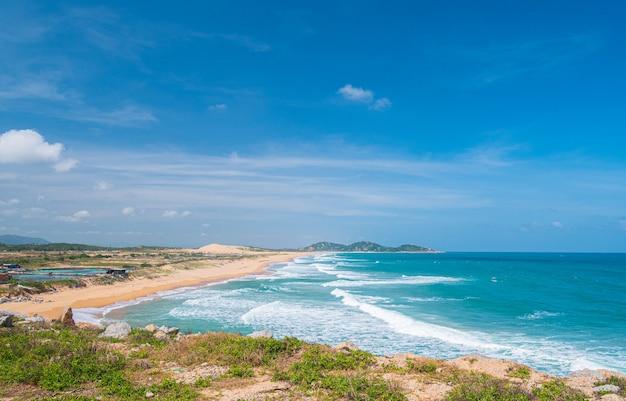 Vista espansiva della pittoresca baia tropicale, mare ondeggiante blu delle splendide dune di sabbia dorate di bai mon. la costa più orientale del vietnam, provincia di phu yen tra da nang e nha trang.