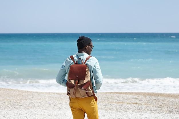 Vista esterna posteriore del giovane turista maschio africano con zaino che indossa abiti alla moda trascorrendo una mattinata di sole in riva al mare, sentendosi felice ed entusiasta di vedere l'oceano per la prima volta nella sua vita