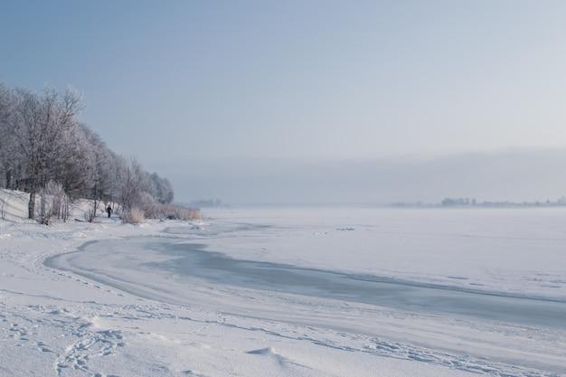 Vista fredda soleggiata fredda di giorno dal fiume e dal parco in inverno