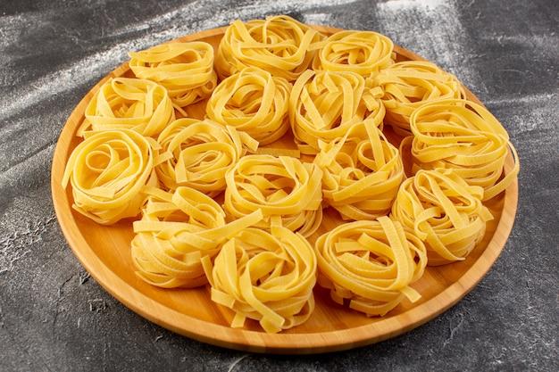 Vista frontale a forma di pasta italiana a forma di fiore crudo e giallo sullo scrittorio di legno