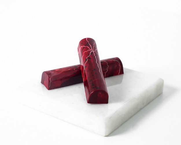 Vista frontale a forma di piastrella di pietre rosse progettata magnificamente sulla superficie bianca