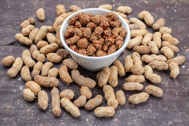 Vista frontale arachidi e noci dolci e appiccicose sulla foto di spuntino dolce di arachidi dado grigio