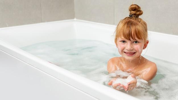 Vista frontale bambina nella vasca da bagno