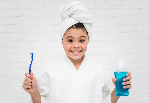 Vista frontale bambina si prepara a lavarsi i denti
