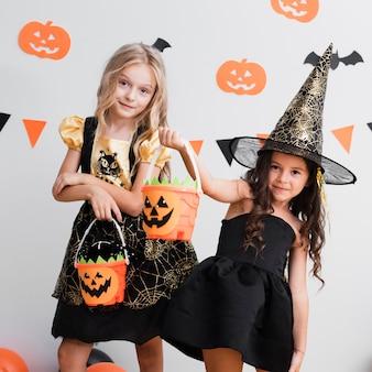 Vista frontale bambine in costume da strega per halloween