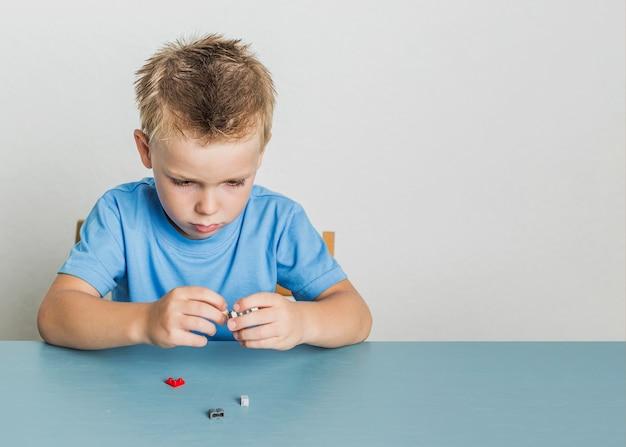 Vista frontale bambino capelli biondi con lego