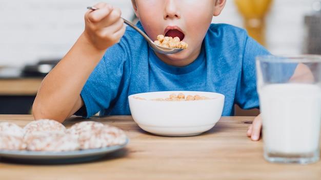 Vista frontale bambino che mangia cereali