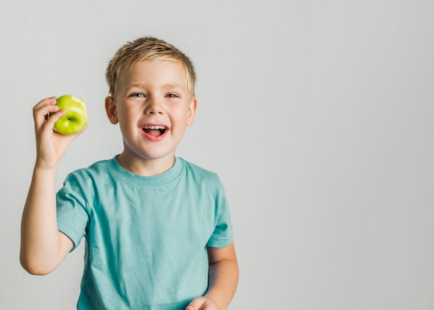 Vista frontale bambino felice con una mela