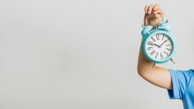Vista frontale bambino in possesso di un orologio
