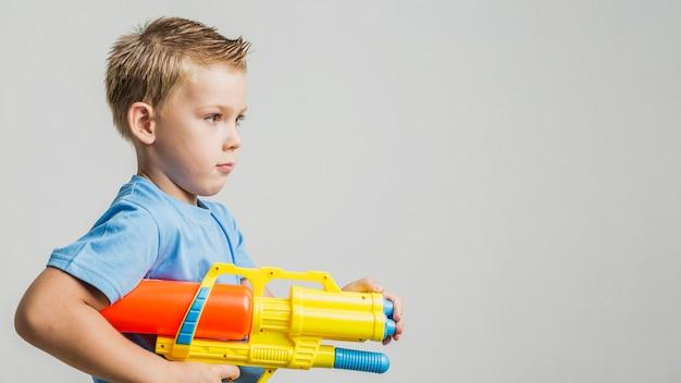 Vista frontale bambino in possesso di una pistola ad acqua