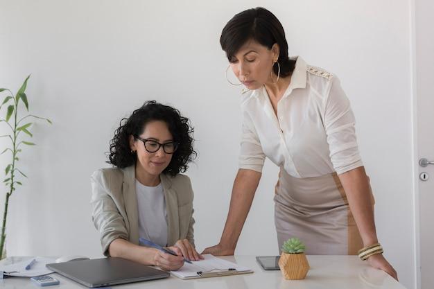 Vista frontale belle donne che lavorano insieme su un progetto