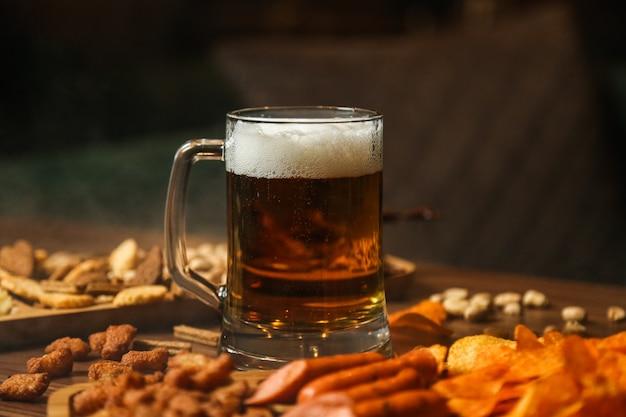 Vista frontale bicchiere di birra con birra snack crostini patatine e salsiccia sul tavolo