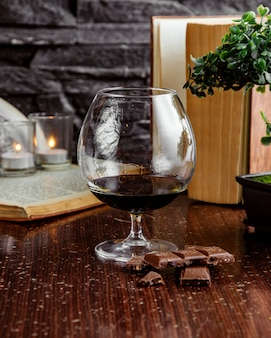 Vista frontale bicchiere di vino rosso con cioccolato
