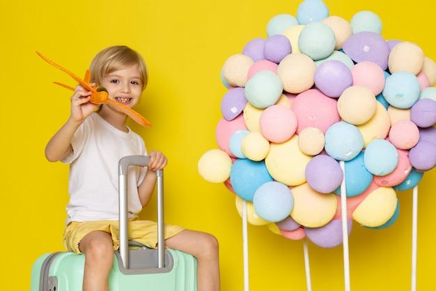 Vista frontale bionda sorridente bambino in maglietta bianca, giocando con l'aereo sulla scrivania gialla