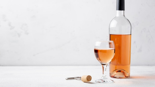 Vista frontale bottiglia di vino rosato e vetro