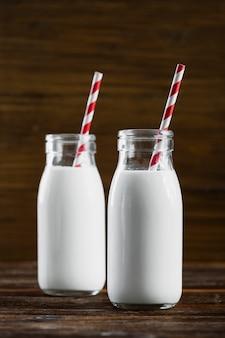 Vista frontale bottiglie di latte con cannucce