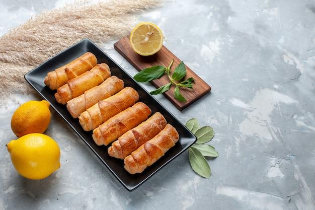 Vista frontale braccialetti dolci con limone sul tavolo luminoso, torta di pasticceria cuocere zucchero dolce