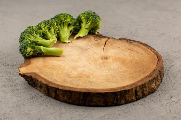 Vista frontale broccoli verdi freschi maturi sulla scrivania in legno marrone e sfondo grigio
