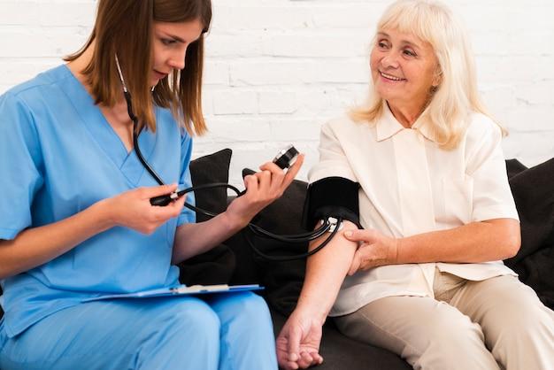 Vista frontale che controlla la pressione sanguigna dell'anziana