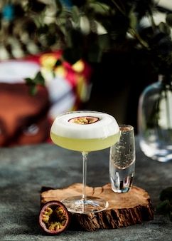 Vista frontale cocktail con frutto della passione su un pezzo di legno