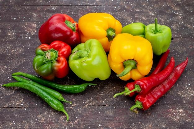 Vista frontale colorati peperoni con peperoni sullo sfondo marrone vegetale colore