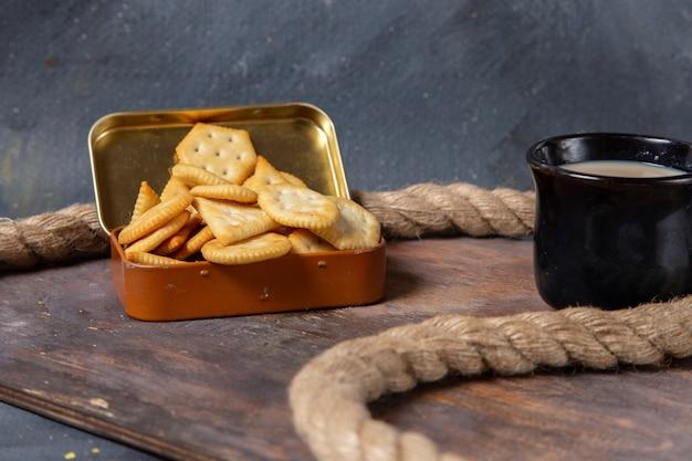Vista frontale cracker salati gustosi con corde sulla scrivania in legno