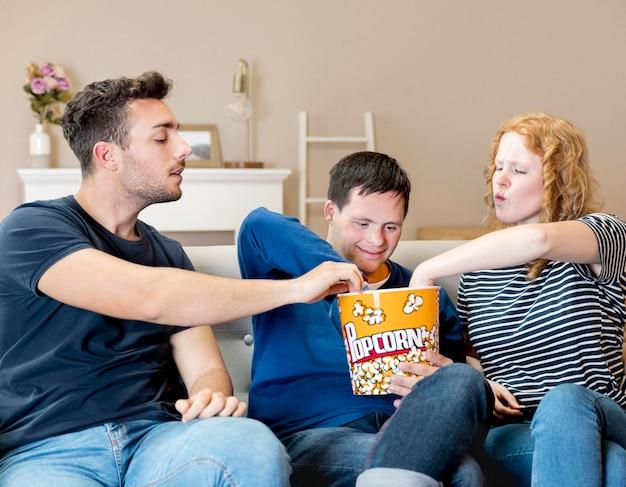Vista frontale degli amici che mangiano popcorn a casa