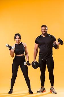 Vista frontale degli atleti che tengono pesi