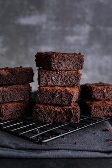 Vista frontale dei brownies sulla griglia di raffreddamento con un panno