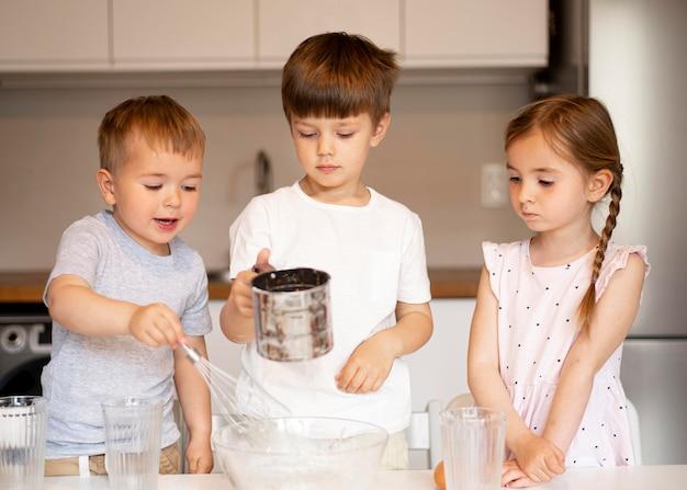 Vista frontale dei fratelli che cucinano a casa