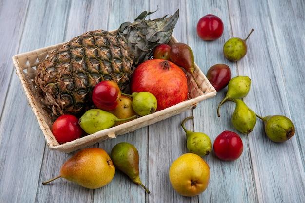 Vista frontale dei frutti come merce nel carrello della prugna della pesca della melagrana dell'ananas e su superficie di legno