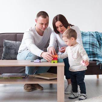 Vista frontale dei genitori che giocano con il bambino a casa