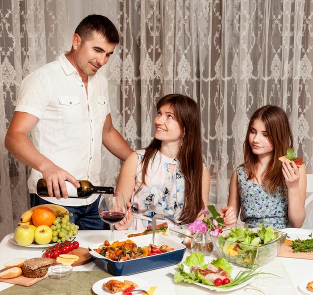 Vista frontale dei genitori che mangiano vino a tavola