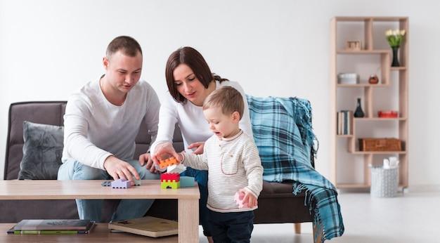 Vista frontale dei genitori e del bambino a casa giocando