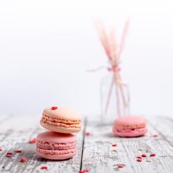Vista frontale dei macarons dei biglietti di s. valentino con i cuori e lo spazio della copia