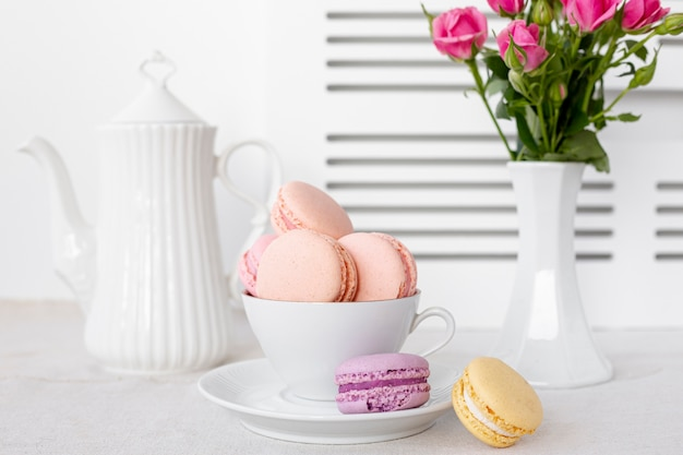 Vista frontale dei macarons in tazza con le rose in vaso