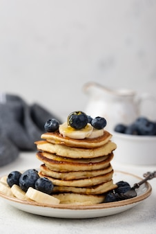 Vista frontale dei pancake della prima colazione con i mirtilli e le fette della banana